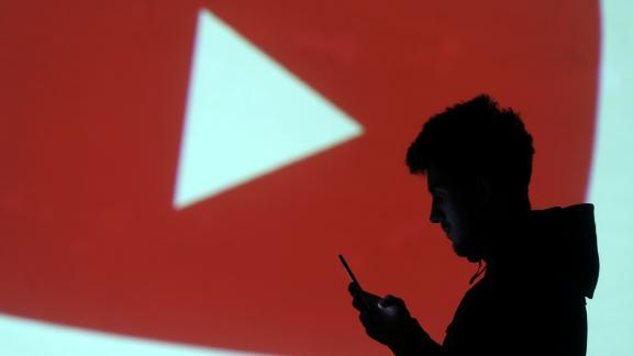 A silhouette of a mobile user is seen next to a screen projection of Youtube logo in this picture illustration taken March 28, 2018.  REUTERS/Dado Ruvic/Illustration