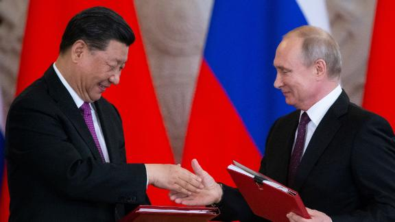 Russian President Vladimir Putin and his Chinese counterpart Xi Jinping exchange documents during a signing ceremony following their talks at the Kremlin in Moscow.