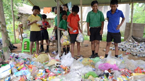 Indian students gather plastic bags before giving them as fees at the Akshar Forum school in Pamohi on the outskirts of Guwahati on May 20, 2019.