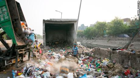 An Indian worker watches a truck dump trash for sorting in New Delhi in April 2019.