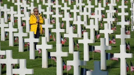 COLLEVILLE-SUR-MER, FRANCE - JUNE 06:  A visitor walks among graves at the Normandy American Cemetery on the 75th anniversary of the World War II Allied D-Day invasion on June 06, 2019 near Colleville-Sur-Mer, France. Veterans, families, visitors, political leaders and military personnel are gathering in Normandy to commemorate D-Day, which heralded the Allied advance towards Germany and victory about 11 months later. Normandy American Cemetery contains the graves of over 9,600 U.S. soldiers killed on D-Day and in the Battle of Normandy.  (Photo by Sean Gallup/Getty Images)