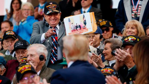 A World War II veteran shows Trump a photo of himself with the President.