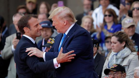 Macron and Trump embrace during the D-Day ceremony.