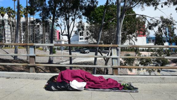 A homeless man sleeps on a sidewalk in Los Angeles on March 10.