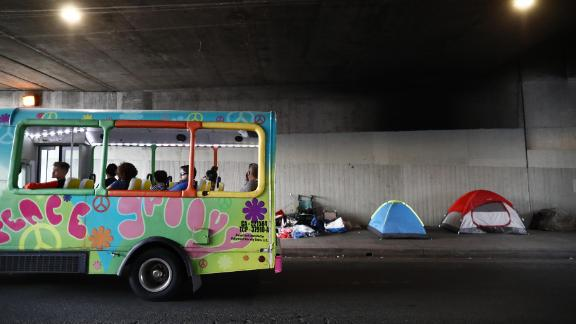A tour bus passes a homeless encampment located beneath an overpass on June 5.