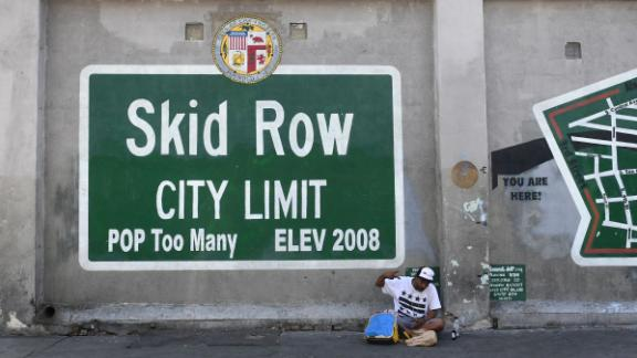 A man gestures while seated beside a Skid Row painting on May 30.