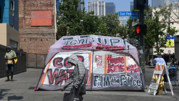 Pedestrians walk past a tent on Skid Row on May 30.