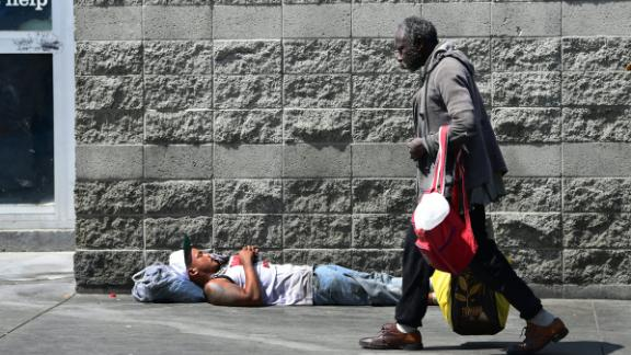 A pedestrian walks past a man sleeping on a sidewalk in Los Angeles on May 30.
