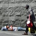 A pedestrian walks past a man sleeping on a sidewalk in Los Angeles on May 30, 2019. - The city of Los Angeles on May 29 agreed to allow homeless people on Skid Row to keep their property and not have it seized, providing the items are not bulky or hazardous. (Photo by Frederic J. BROWN / AFP) (Photo credit should read FREDERIC J. BROWN/AFP/Getty Images)