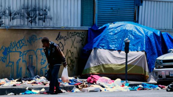 A homeless man walks along a street lined with trash across from a Los Angeles police station on May 30.