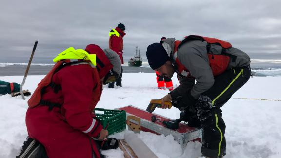 Scientist Till Wagner & team member measuring the thickness and density of a recently extracted ice core that holds frozen clues from an ice floe drifting down the Fram Strait.