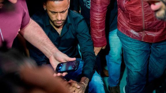 Brazil's star striker Neymar arrives at the police station in a wheelchair.