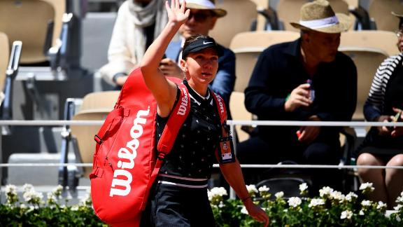 Simona Halep waves to the crowd after losing to Amanda Anisimova at the French Open.