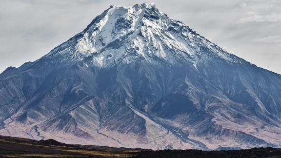 Beautiful autumn volcanic landscape - view of snow-capped cone of stratovolcano Bolshaya Udina Volcano in Klyuchevskaya Group of Volcanoes. Russian Far East, Kamchatka Peninsula, Eurasia.; Shutterstock ID 753658408; Job: -