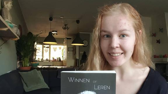 "Noa Pothoven posing with her award-winning autobiography, titled Winnen of Leren (""Winning or Learning"")."