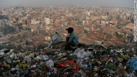 A young Indian ragpicker looks over New Delhi after collecting usable material from a garbage dump at the Bhalswa landfill site in October 2018.