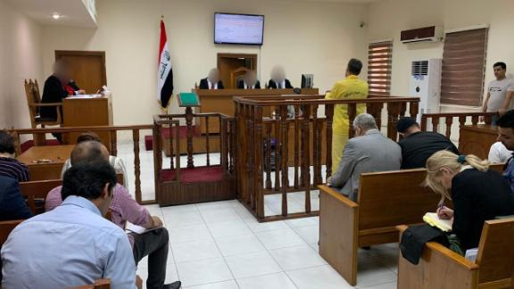 Murad Mohammad Mustafa stands with his back to the camera at the Iraqi court in in Baghdad on Monday, June 3.