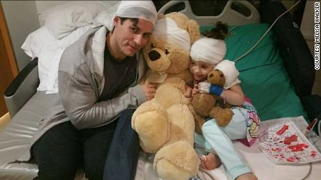 Alex Walker, 7, and her father squeeze her teddy bears while she's hospitalized for epilepsy.