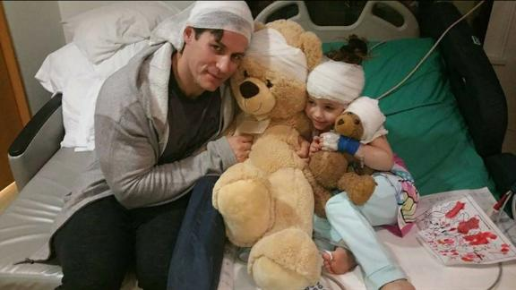 Alex Walker, 7, and her father squeeze her teddy bears while she