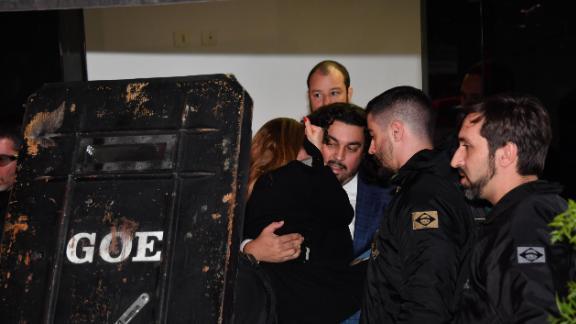 Najila Trindade is carried by her lawyer Danilo Garcia de Andrade to a police car.