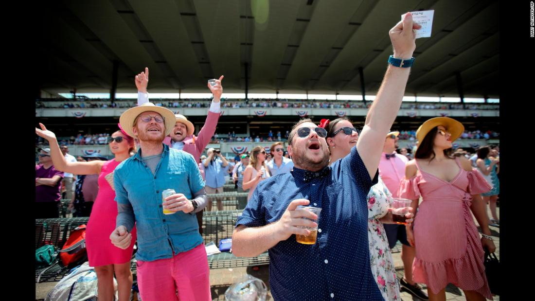 Spectators cheer during one of the early races before the 151st running of the Belmont Stakes.