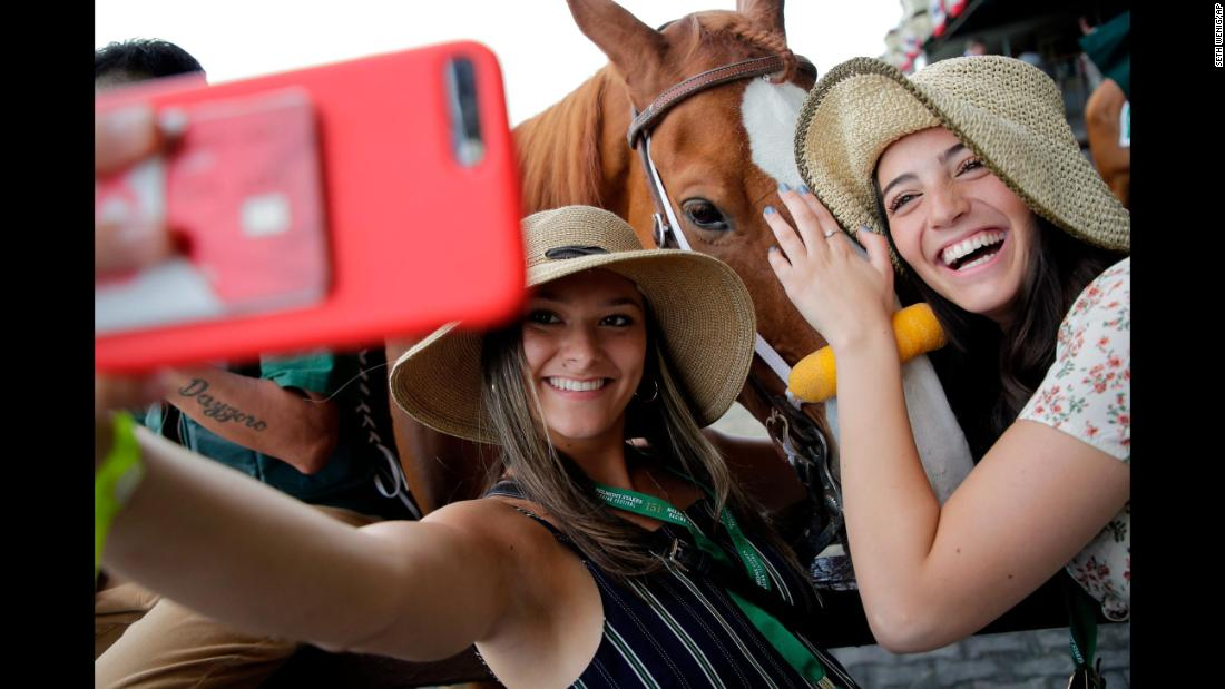 From left, Spectators Maddie Berry and Carly Zakarin pose for a selfie with horse Red Shogun.