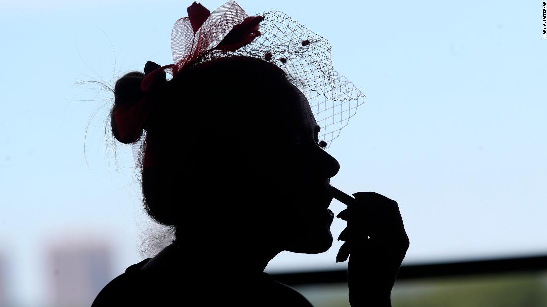 Joanne Principe touches up her lipstick while watching an early race before the running of the Belmont Stakes.