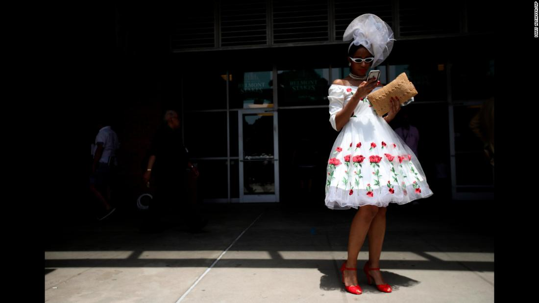 Mekeda Grant, of Brooklyn, checks her phone while walking through the grandstand.