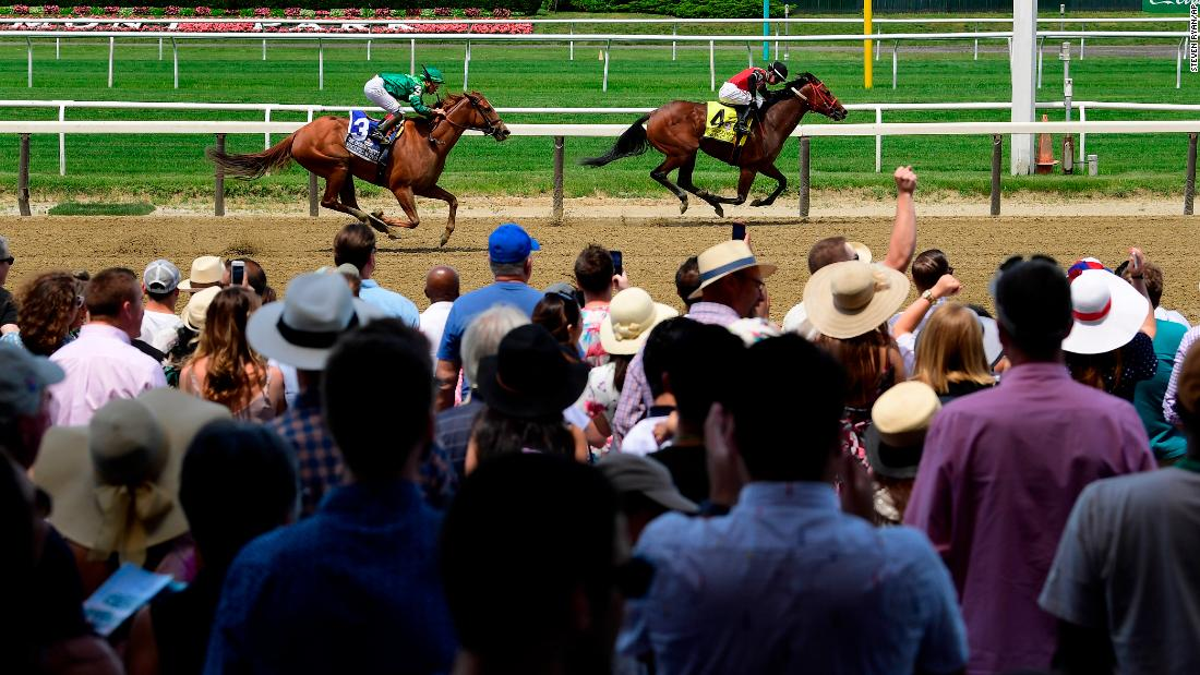 From left, Pacific Wind and Escape Clause approach the finish line during the fifth race of the day before the 151st running of the Belmont Stakes.