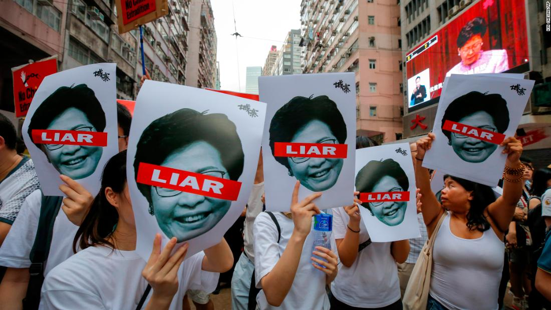 Protesters hold pictures of Hong Kong Chief Executive Carrie Lam on Sunday, June 9.