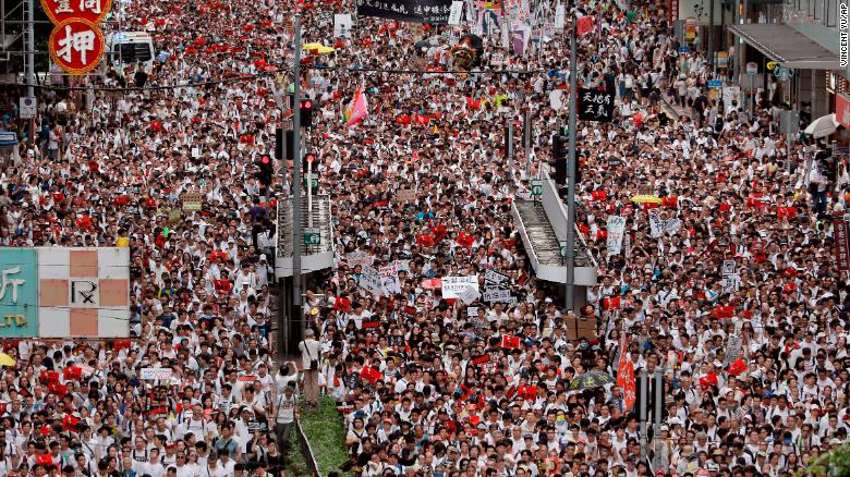 People march down a street in downtown Hong Kong to protest a controversial extradition bill on Sunday, June 9.