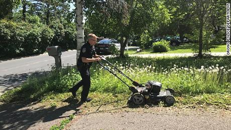 Orono Police Officer Matt Siltala mows a resident's lawn.