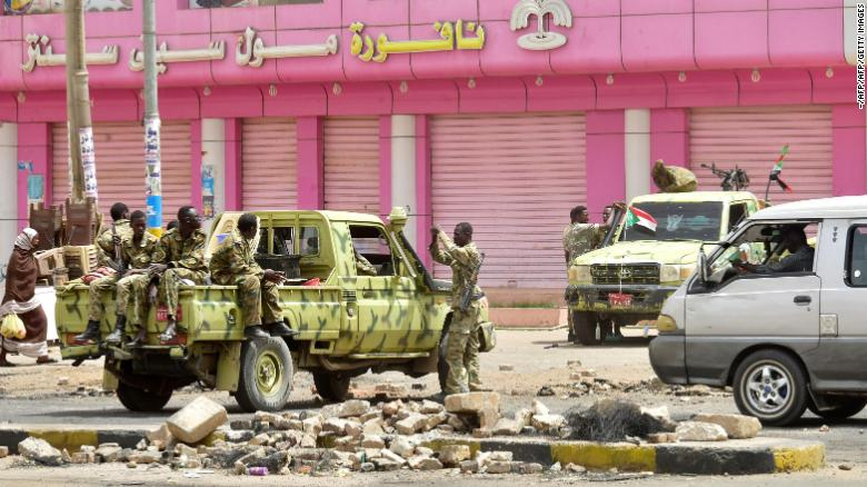 Sudanese soldiers guard a street in Khartoum on Sunday after police fired tear gas at protesters.