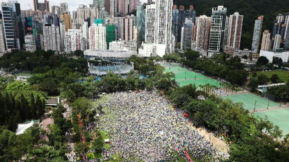 """Protesters waved placards and wore white -- the designated color of the rally. """"Hong Kong, never give up!"""" some chanted."""