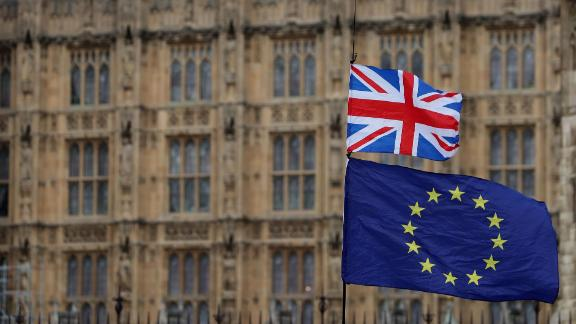 """TOPSHOT - An anti-Brexit activist waves a Union and a European Union flag as they demonstrate outside the Houses of Parliament in central London on January 23, 2019. - Britain's main opposition Labour party has proposed MPs be allowed to vote on a second referendum as part of a series of options to stop a """"no deal"""" Brexit. (Photo by Daniel LEAL-OLIVAS / AFP)        (Photo credit should read DANIEL LEAL-OLIVAS/AFP/Getty Images)"""