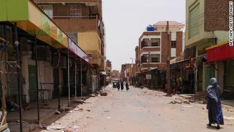 A Sudanese woman walks past closed shops in a commercial street in Khartoum's twin city Omdurman on June 9.