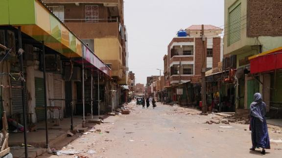 A Sudanese woman walks past closed shops in a commercial street in Khartoum's twin city Omdurman on June 9.