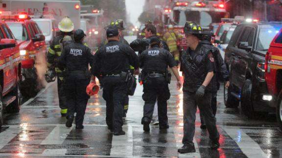 New York police and firefighters arrive at the helicopter crash scene Monday in Midtown Manhattan.