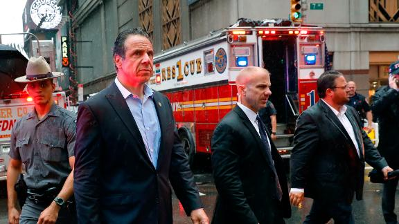 New York Gov. Andrew Cuomo, center, walks near the scene where a helicopter was reported to have crash landed on top of a building in midtown Manhattan, Monday, June 10, 2019, in New York.  (AP Photo/Mark Lennihan)