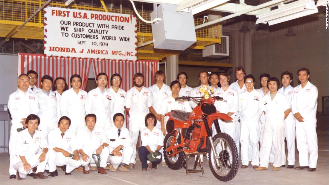 Associates pose alongside the CR250R motorcycle model at Honda's first motorcycle plant.