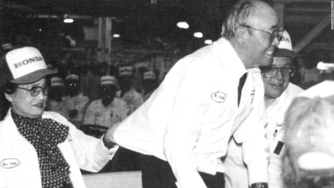 Soichiro Honda's wife clutches his shirt to prevent him falling while he bows and greets associates at the Marysville plant.