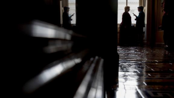 Klobuchar, right, talks with Sen. Debbie Stabenow in a Capitol Hill hallway in November 2016.