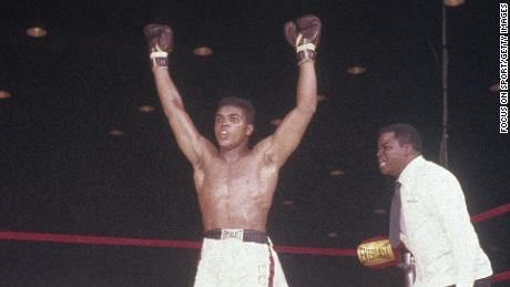 Cassius Clay, later Muhammad Ali, with his hands raised in victory over Sonny Liston on February 25, 1964 at Convention Hall in Miami, Florida.