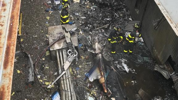 New York City firefighters work at the scene of the helicopter crash Monday.