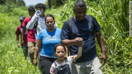 A Honduran family heading to the US tries to avoid detection by Mexican authorities on the outskirts of Huixtla on June 9.