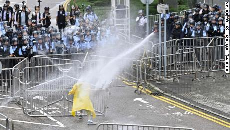 Police officers deploy a water cannon on June 12, 2019, to a single demonstrator near the Hong Kong government headquarters. 2019.