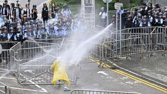 Police officers use a water canon on a lone protester near the government headquarters in Hong Kong on June 12, 2019.