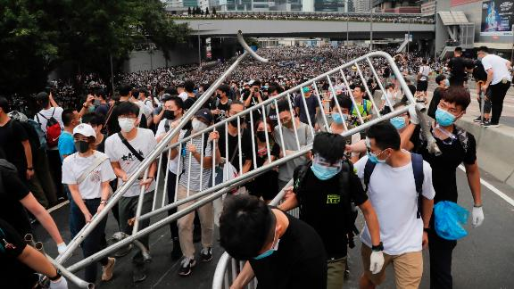 Protesters carry barricades as they march toward the Legislative Council.