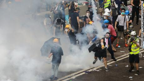 A protester throws a tear gas canister fired by police during a rally against a controversial extradition law proposal outside the government headquarters in Hong Kong on June 12, 2019. - Violent clashes broke out in Hong Kong on June 12 as police tried to stop protesters storming the city's parliament, while tens of thousands of people blocked key arteries in a show of strength against government plans to allow extraditions to China. (Photo by DALE DE LA REY / AFP)