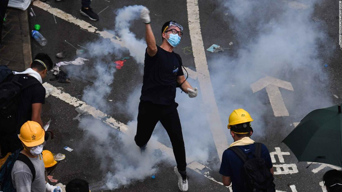 A protester returns a tear-gas canister fired by police during clashes outside the government headquarters in Hong Kong on Wednesday, June 12.
